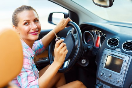 engine: Woman sitting in a convertible and is going to start the engine - the concept of buying a used car or a rental car
