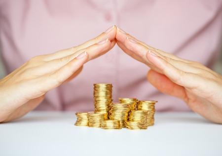 ganancias: Proteja nuevo concepto de puesta en marcha de negocios - con las manos y monedas Foto de archivo