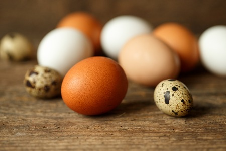 product range: Fresh chicken and quail eggs on a wooden rustic background