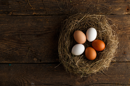 product range: Fresh chicken eggs in a nest on a wooden rustic background Stock Photo