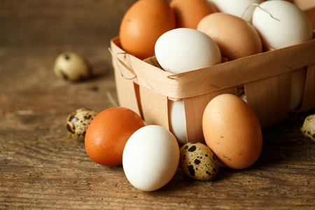 gamme de produit: Fresh chicken and quail eggs on a wooden rustic background