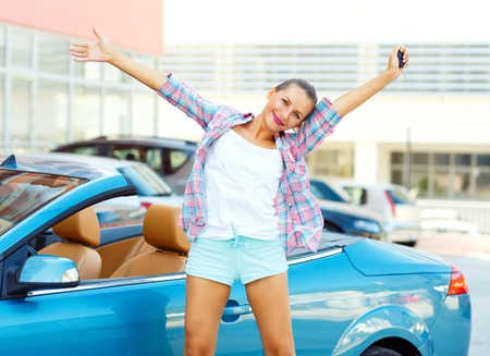 car service: Young emotional woman standing near a convertible with the keys in her hand - concept of buying a used car or a rental car Stock Photo