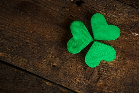 clovers: Green shamrock clovers on wooden background. Background for St. Patricks Day celebration