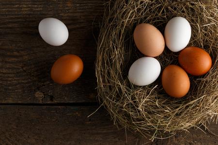 gamme de produit: oeufs de poulet frais dans un nid sur un fond en bois rustique Banque d'images