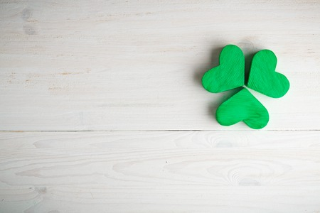 Green shamrock clovers on white wooden background. Background for St. Patrick's Day celebration