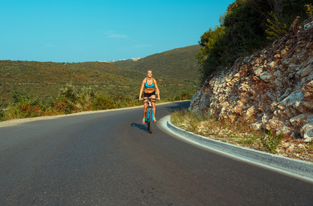 mountain bicycles: Happy woman cyclist riding a bike on a mountain road