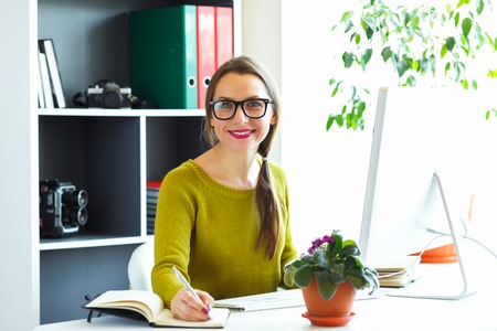 telecommuting: Beautiful young woman working from home - modern business concept