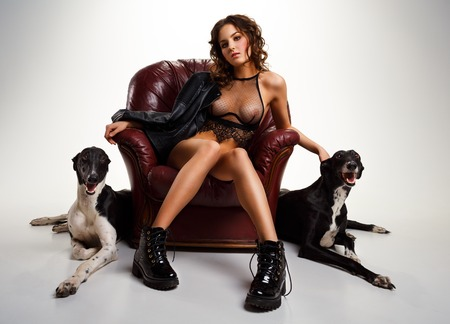 dark haired woman: Sexy dark haired woman in black lingerie posing in a chair with greyhound dogs