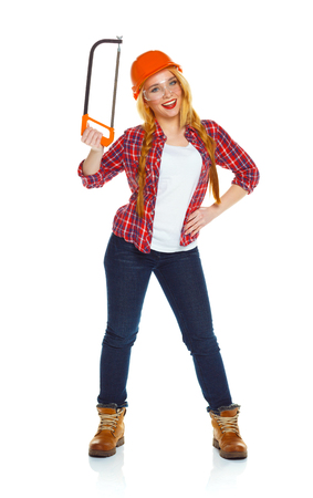 serrate: Young funny woman in helmet with a saw on a white background Stock Photo