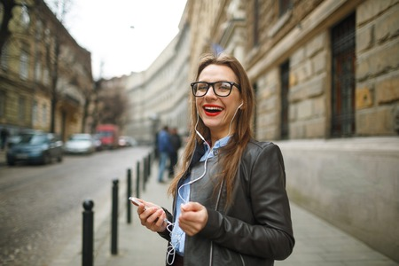 sidewalk talk: Businesswoman walking down the street while using the smart phone. Happy smiling caucasian business woman busy