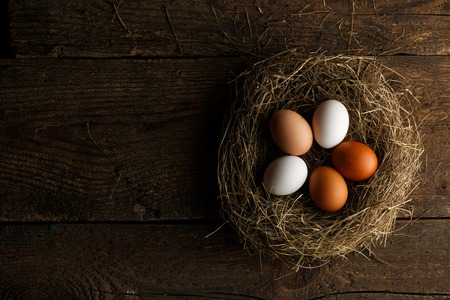 gamme de produit: Fresh chicken eggs in a nest on a wooden rustic background Banque d'images