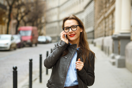 sidewalk talk: Businesswoman on cellphone walking down the street while talking on smart phone. Happy smiling caucasian business woman busy