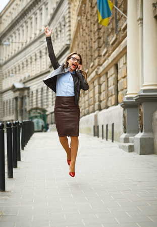 sidewalk talk: Delighted business woman jumping for joy while talking on the smart phone on the street