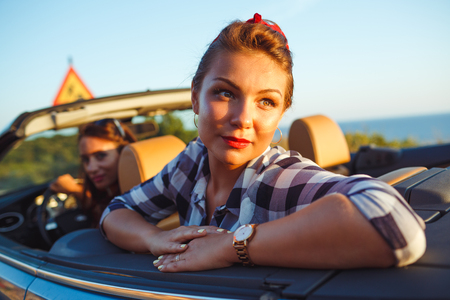 cabriolet: Two young happy girls driving a cabriolet, summer vacations concept