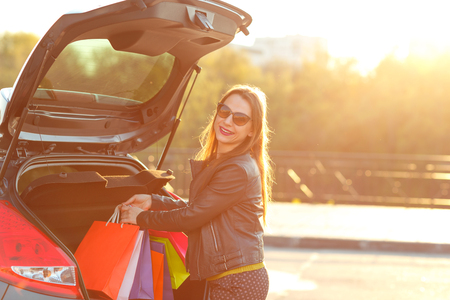 car trunk: Smiling Caucasian woman putting her shopping bags into the car trunk