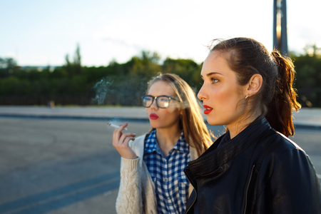 malos habitos: Two beautiful young girls to smoke while waiting - concept of bad habits Foto de archivo