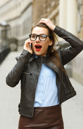 sidewalk talk: Pretty surprised businesswoman walking down the street while talking on smart phone