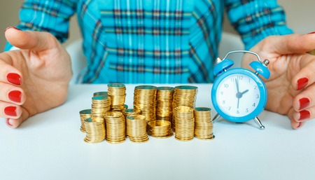 secure growth: Protect new business start-up concept - with hand, coin and and blue alarm clock