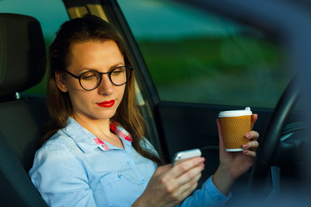 distraction: Young businesswoman sending a text message and drinking coffee while driving a car