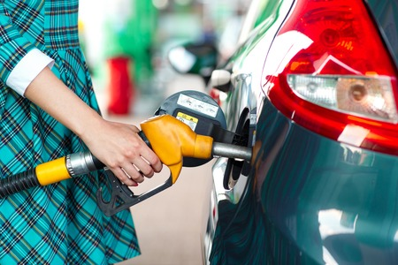 fills: Woman fills petrol into her car at a gas station