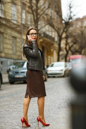 sidewalk talk: Businesswoman walking down the street while talking on smart phone. Caucasian business woman busy Stock Photo
