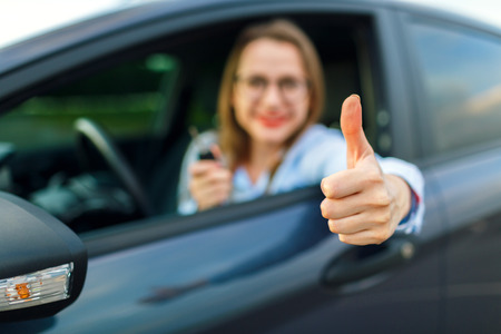 thumb keys: Young happy woman sitting in a car with the keys in her hand and thumb up - concept of buying a used car or a rental car