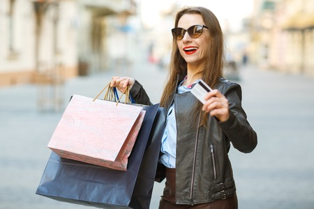 overspending: Sale, shopping, tourism and happy people concept - beautiful woman with shopping bags and credit card in the hands on a street