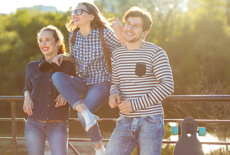 friends having fun: Friendship, leisure, summer, technology and people concept - smiling friends having fun outdoors Stock Photo