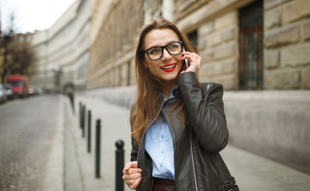 phone professional: Businesswoman walking down the street while talking on smart phone. Happy smiling caucasian business woman busy