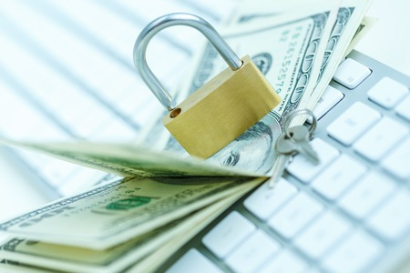 theft prevention: Security lock on dollar bills with white computer keyboard - breach of security online payments concept