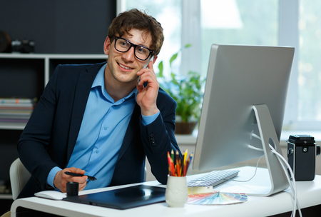 telecommuting: Handsome young man working from home office - modern business concept Stock Photo
