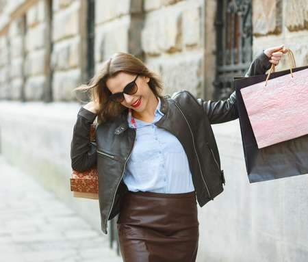 gift spending: Sale, shopping, tourism and happy people concept - beautiful woman with shopping bags in the ctiy