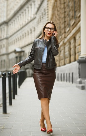 sidewalk talk: Businesswoman walking down the street while talking on smart phone. Caucasian business woman busy Stock Photo