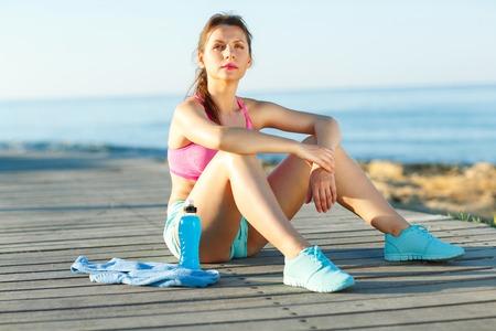 Soleado por la mañana en la playa, mujer atlética de descanso después de correr en el entrenamiento de la mañana por el mar