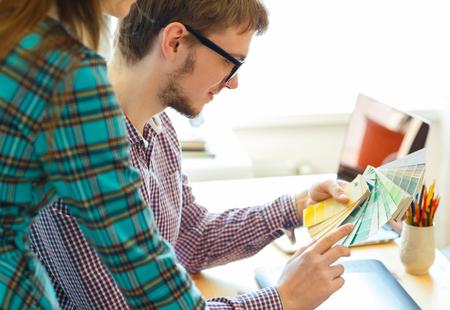 empleada domestica: colega joven - hombre y una mujer mirando a una paleta de color de la pintura en la oficina en casa, concepto de negocio moderno