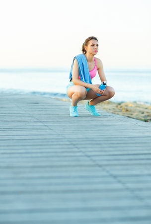 hacer footing: Sunny morning on the beach, athletic woman resting after running at the morning training by the sea