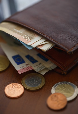 capitalization: Brown leather wallet with euro money inside and coins, credit cards near it