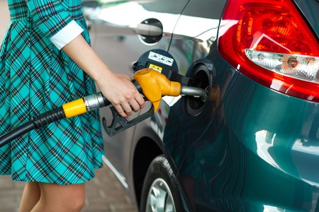 unleaded: Woman fills petrol into her car at a gas station closeup