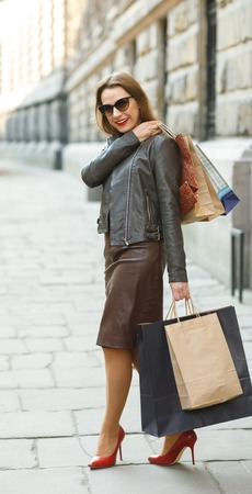 overspending: Sale, shopping, tourism and happy people concept - beautiful woman with shopping bags in the ctiy