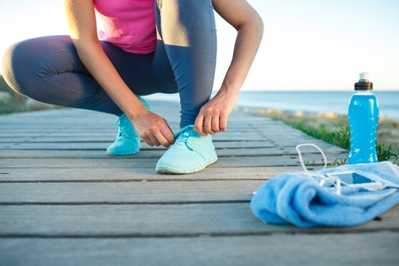 getting late: Running shoes - woman tying shoe laces. Closeup of female sport fitness runner getting ready for jogging outdoors on waterfront in late summer or fall