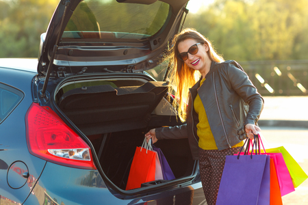 go to the shopping: Smiling Caucasian woman putting her shopping bags into the car trunk- Lets go shopping concept
