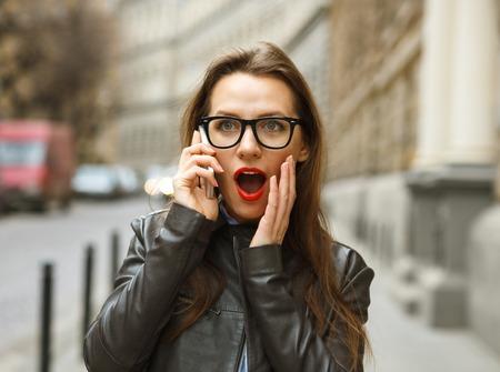 sidewalk talk: Surprised businesswoman walking down the street while talking on smart phone Stock Photo