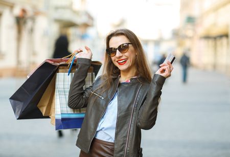 go to the shopping: Beautiful woman with shopping bags and credit card in the hands on a street- Lets go shopping concept