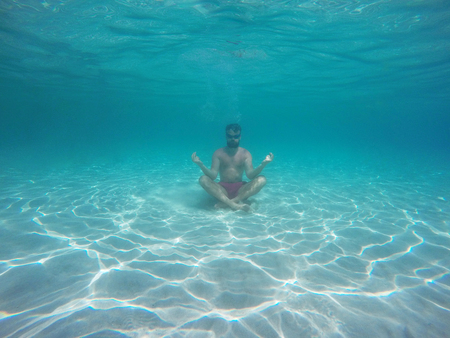 lotus position: Young beard man with glasses in the lotus position meditating under water Stock Photo