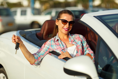 caras emociones: Young pretty woman sitting in a convertible car with the keys in hand - concept of buying a used car or a rental car
