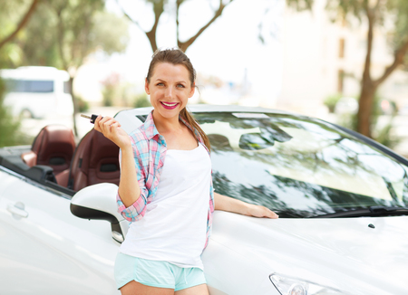 Young pretty woman standing near convertible with keys in hand - concept of buying a used car or a rental car