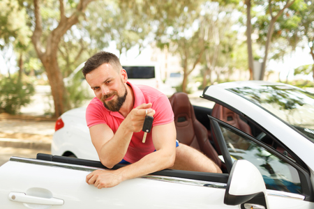 Young bearded man standing near convertible with keys in hand - the concept of buying a used car or rent a car