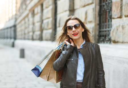 overspending: Sale, shopping, tourism and happy people concept - beautiful woman with shopping bags in the ctiy - Lets go shopping concept