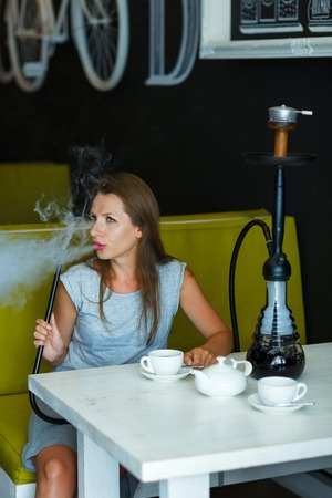 turkish ethnicity: Beautiful young woman smoking a hookah and drinking tea in a cafe