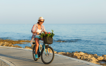 Carefree pretty woman with bicycle riding on a wooden path at the sea, having fun and smiling Stock Photo